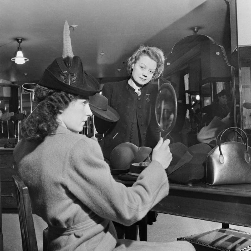 A customer tries on a new hat in the millinery department of Bourne and Hollingsworth on Londons Oxford Street in 1942  D6596